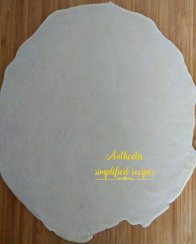 Rolls a portion of dough into a sheet of uniform thickness of about 2-3 mm